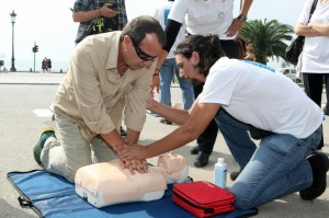 People practicing CPR on a mannequin, with the instructor's help